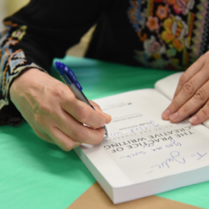 Heather signing a book on a green table