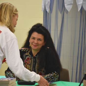 Heather sits behind a green book signing table