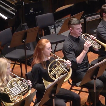 Hannah plays the French Horn next to other ensemble players