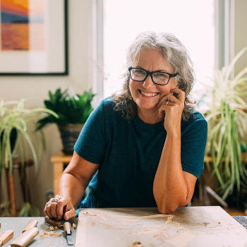 Mary sits at her studio desk. She is wearing a teal shirt and smiling.