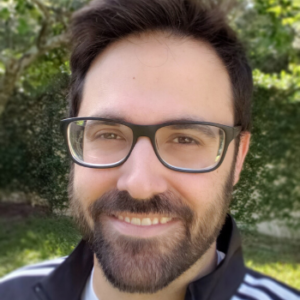 Jarod Roselló wearing glasses and smiling in front of a leafy green tree