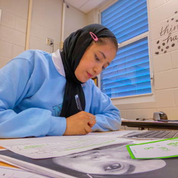 Yasmeen sits at her writing desk. She is wearing a blue sweatshirt and black head scarf.